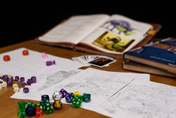 Dungeons and dragons books and dice on table.