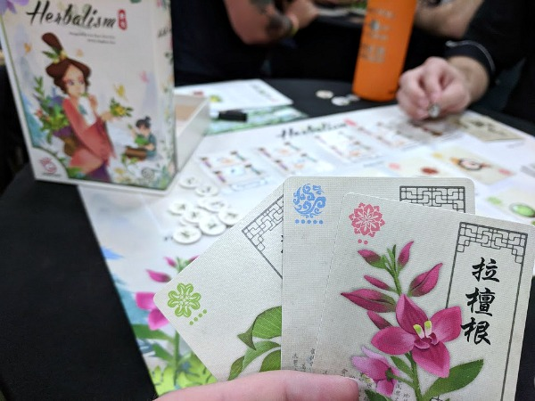 Playing demo of Herbalism game at Origins Game Fair