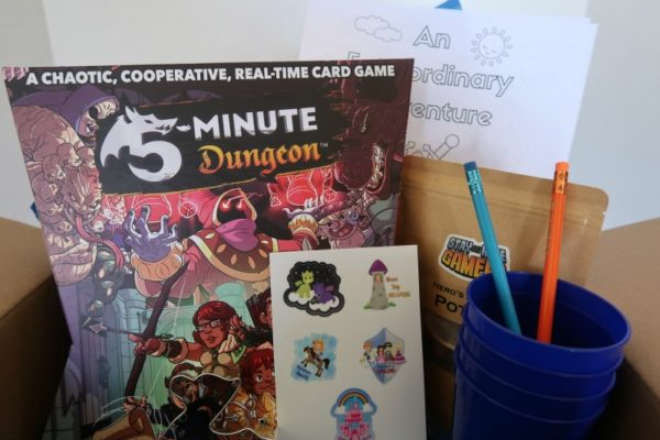 Board game, stickers, and other items in the curated family game night box.