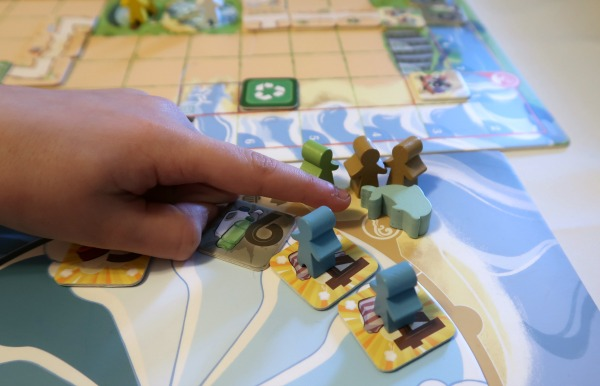 Dolphin game piece and meeples on the Ocean Crisis game board.