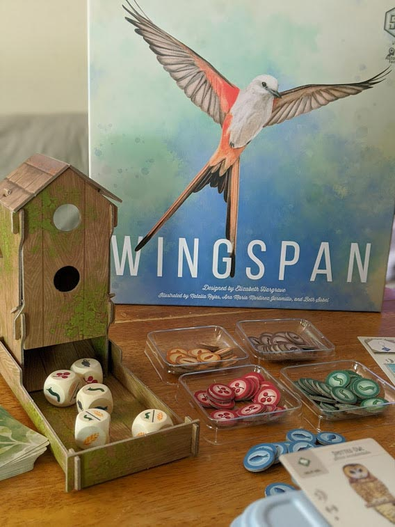 Game box for Wingspan standing up behind bird feeder dice tower and other game components on table.