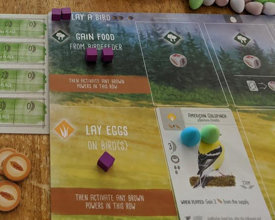 Purple wooden action cubes on Wingspan player mat as well as bird cards and eggs. Goal tracker card and food tokens to the left of the mat.