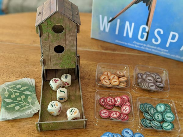 Overhead view of cardboard dice tower that looks like a bird feeder with custom wooden dice in the tray next to food tokens.