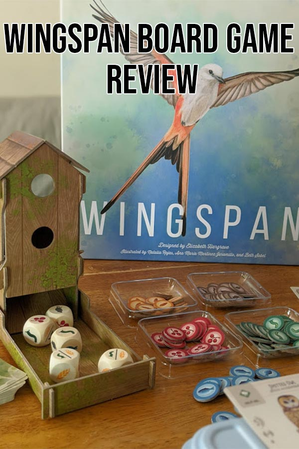 Game components set out on table in front of Wingspan game box with text overlay stating Wingspan Board Game Review.