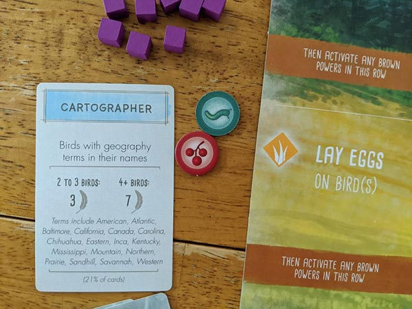 Cartographer bonus objective card for Wingspan on table next to food tokens and player mat.